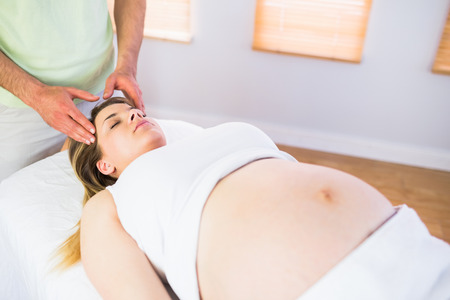 woman relax: Relaxed pregnant woman enjoying head massage in a studio