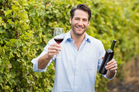 seasonal worker: Young happy man smiling at camera and holding a glass of wine in the grape fields