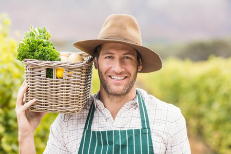 young farmer: Young happy farmer holding a basket of vegetables in the field Stock Photo