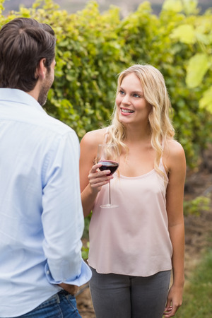 mid adult couple: Young happy woman smiling at young man in the grape fields