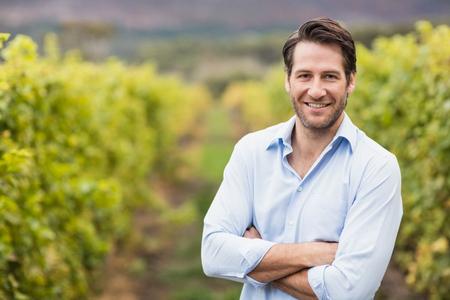 persona alegre: Viticultor feliz con los brazos cruzados en los campos