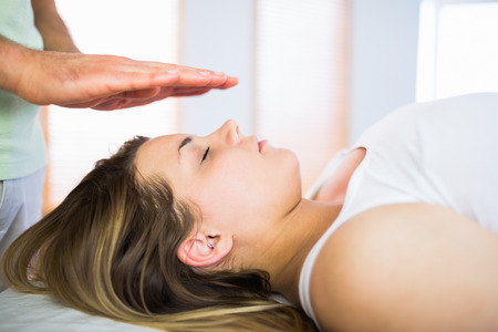 reiki: Close up view of pregnant woman getting reiki treatment in a studio