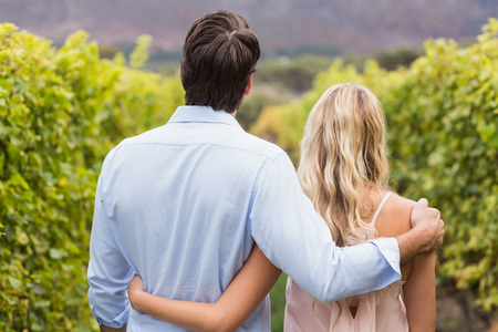 arm around: Young happy couple having an arm around each other in the grape fields Stock Photo