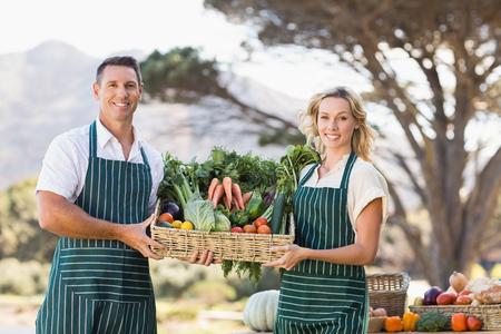 Portrait of a smiling farmer couple holding a vegetable basket