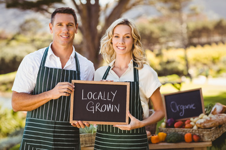 living together: Portrait of a farmer couple holding locally grown sign Stock Photo