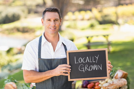 locally: Portrait of a smiling farmer holding a locally grown sign