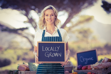locally: Portrait of a farmer woman holding a locally grown sign