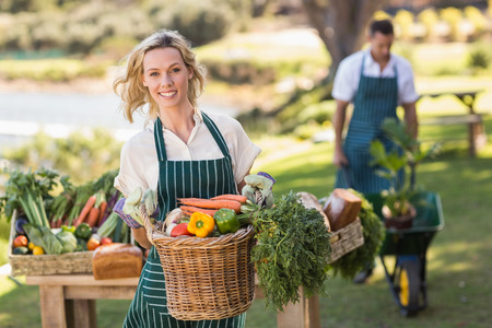 granjero: Retrato de una mujer granjero que sostiene una cesta de verduras
