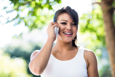 phoning: Portrait of smiling athletic woman phoning with smartphone in the city