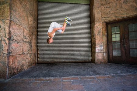 somersault: Extreme athlete doing a front flip in front of a building in the city Stock Photo