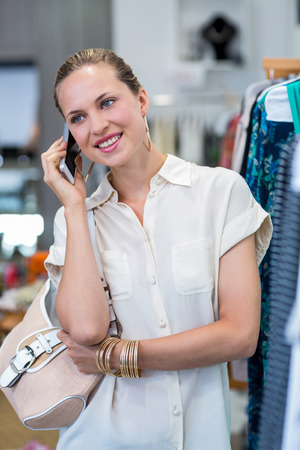 clothes rail: Smiling woman phoning next to clothes rail in clothing store Stock Photo
