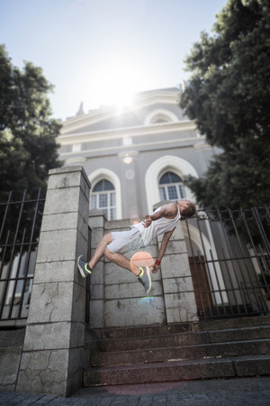 backflip: Extreme athlete doing a backflip in front of a building in the city Stock Photo