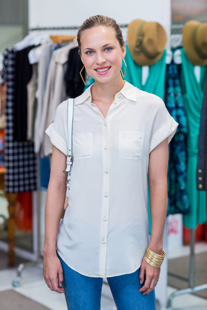clothes rail: Portrait of smiling woman in front of clothes rail in clothing store Stock Photo