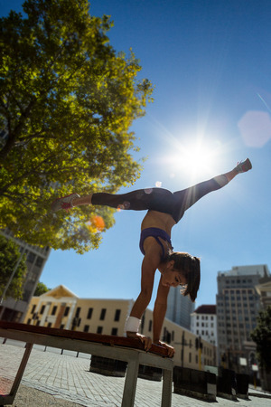 handstand: Athletic woman performing handstand and doing split on bench in the city Stock Photo