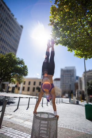 handstand: Athletic woman performing handstand on bin in the city