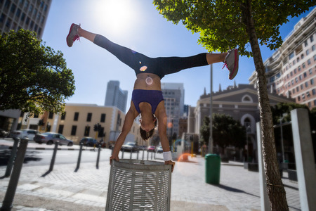handstand: Athletic woman performing handstand and doing split on bin in the city