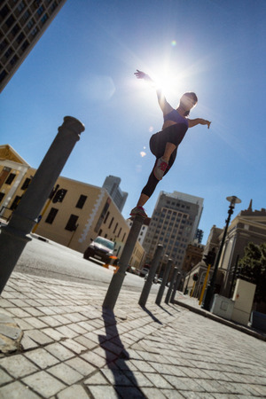 bollard: Athletic woman balancing on bollard in the city