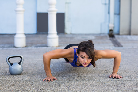 standing up: Focused athletic woman doing push-ups in the city Stock Photo