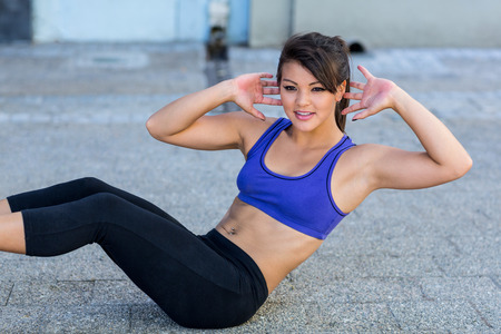 sit up: Smiling athletic woman doing sit-ups in the city Stock Photo