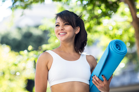 athlete: Smiling athletic woman carrying yoga mat in the city