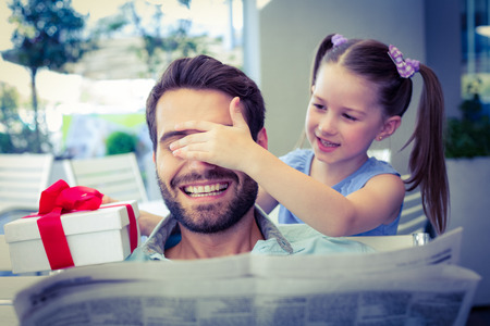 father with child: Daughter offering her present to her dad in the cafe Stock Photo