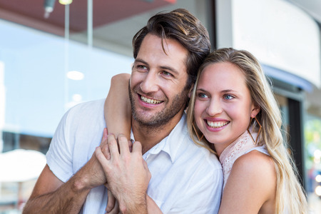 arm around: Smiling woman putting arm around her boyfriend at shopping mall Stock Photo