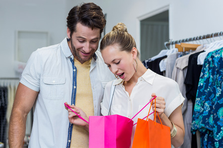 clothing store: Happy couple looking into shopping bags in clothing store Stock Photo