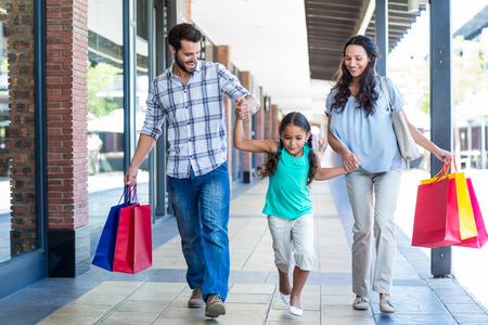 chicas de compras: Familia feliz con bolsas de compras en el centro comercial