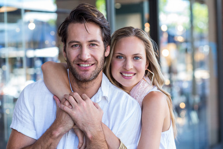 arm around: Portrait of smiling woman putting arm around her boyfriend at shopping mall