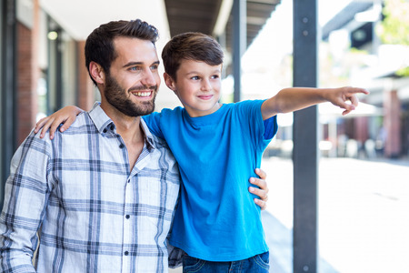 one parent: Son and father look away at the mall Stock Photo