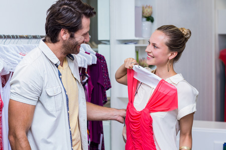 clothing store: Smiling woman showing red dress to boyfriend in clothing store Stock Photo