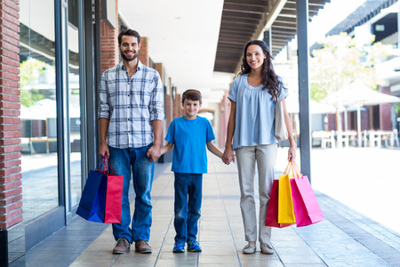 niños de compras: Familia feliz con bolsas de compras en el centro comercial