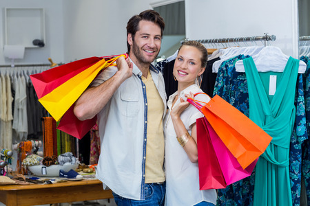 clothing store: Smiling couple with shopping bags in clothing store