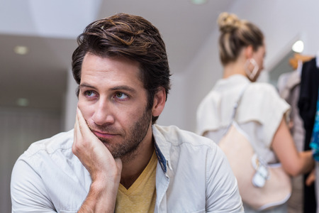 Bored man sitting in front of his girlfriend in clothing store