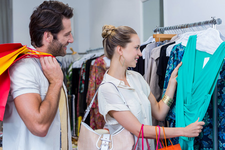 clothing store: Smiling couple browsing clothes in clothing store