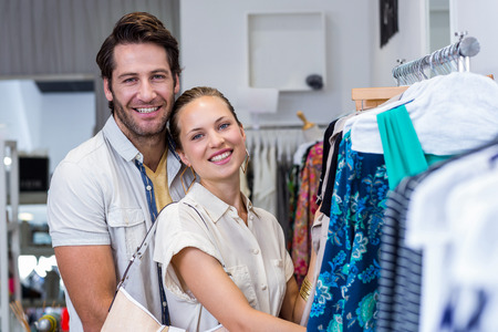 clothing store: Portrait of smiling couple browsing clothes in clothing store Stock Photo