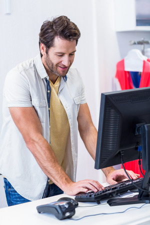 clothing store: Smiling cashier typing in clothing store Stock Photo