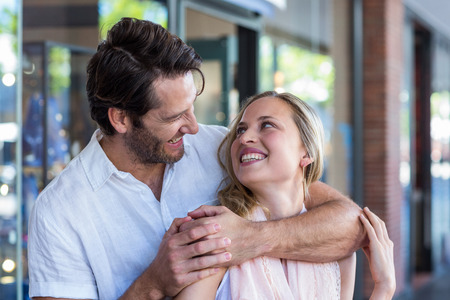 arm around: Smiling man putting arm around his girlfriend and looking at her at shopping mall Stock Photo
