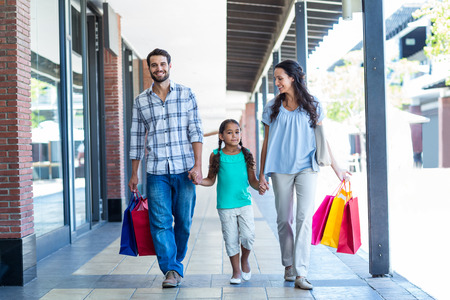 chicas comprando: Familia feliz con bolsas de compras en el centro comercial