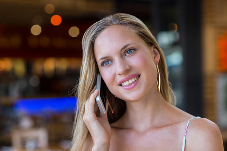 phoning: Smiling attractive woman phoning with smartphone at shopping mall