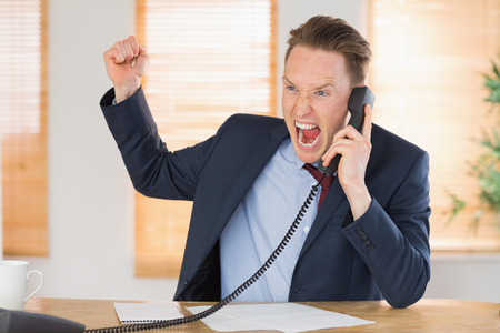 outraged: Furious businessman outraged on the phone in his office