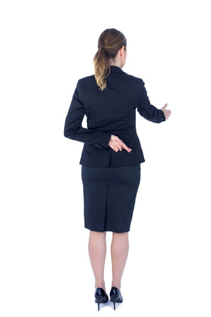 finger crossed: Pretty businesswoman with finger crossed  against a white wall Stock Photo