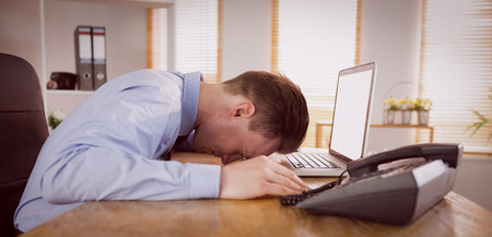 hit tech: Stressed businessman with head on laptop in his office