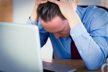 Stressed zakenman met hoofd in de handen bij het kantoor Stockfoto