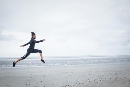 raffreddore: Fit ragazza di lavoro il giorno di freddo in spiaggia