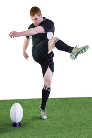 rugby player: Determined rugby player doing a drop kick Stock Photo