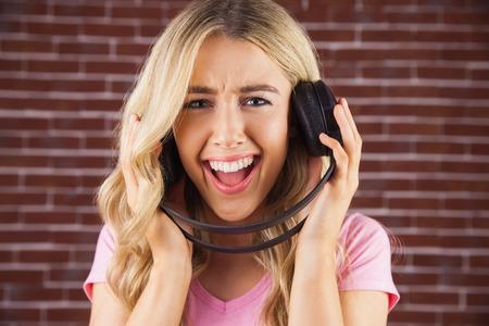 cantando: Retrato de una mujer hermosa con los auriculares que canta contra una pared de ladrillo rojo