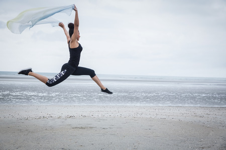 scarf beach: Fit girl leaping with scarf at the beach