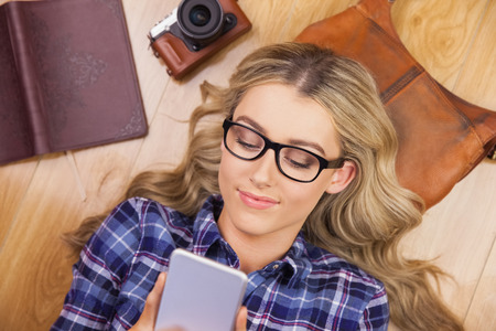 lady on phone: Gorgeous smiling blonde hipster using smartphone and lying on wooden floor