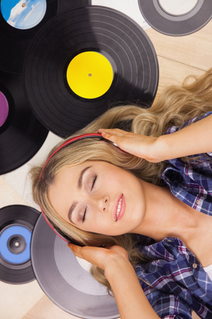 thrift store: A beautiful woman with headphones lying against vinyl Stock Photo